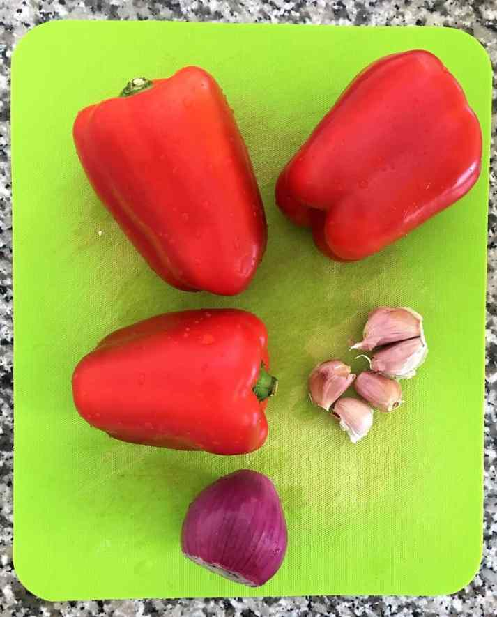 red peppers, garlic and onion on a green cutting board