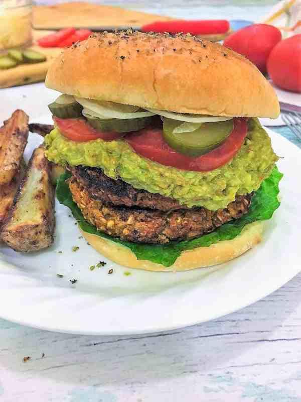 veggie burgers in bun with tomato, pickles, guacamole, and lettuce