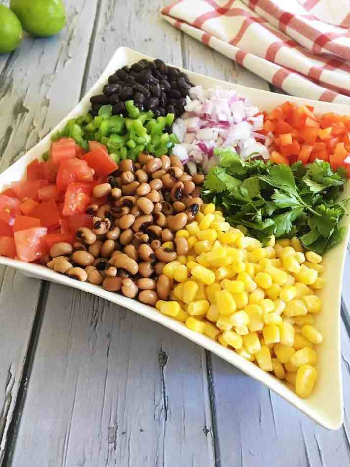 corn, beans, tomatoes, cilantro, red pepper, onion in white dish