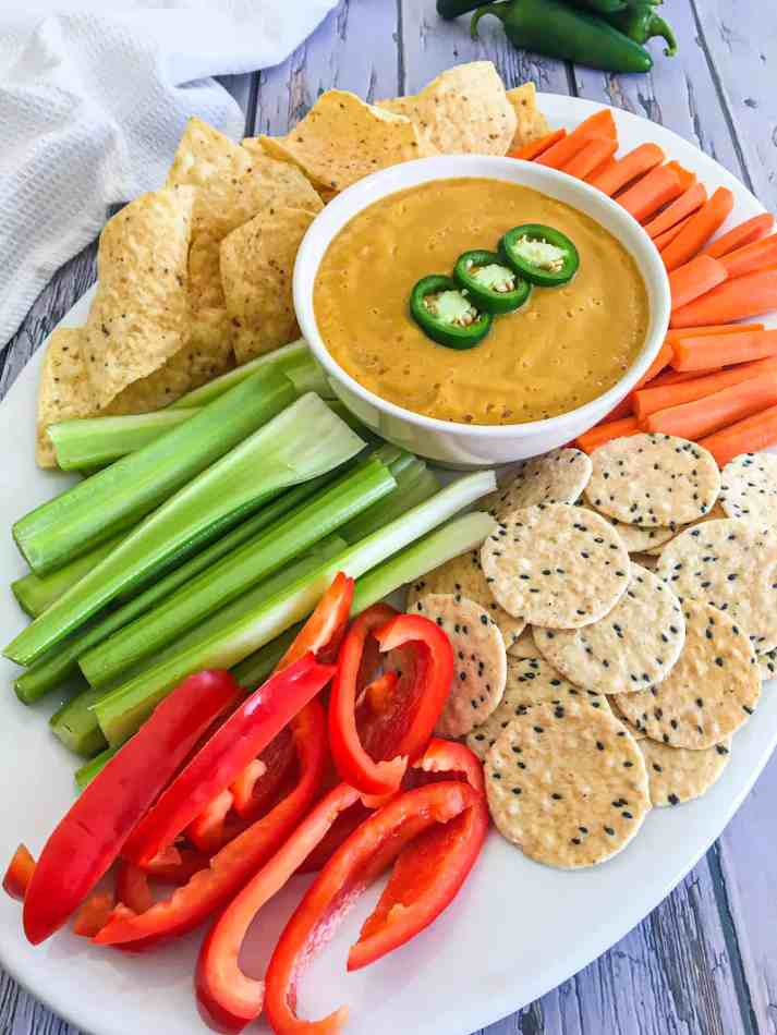 dip in white bowl surrounded by veggies, crackers and chips
