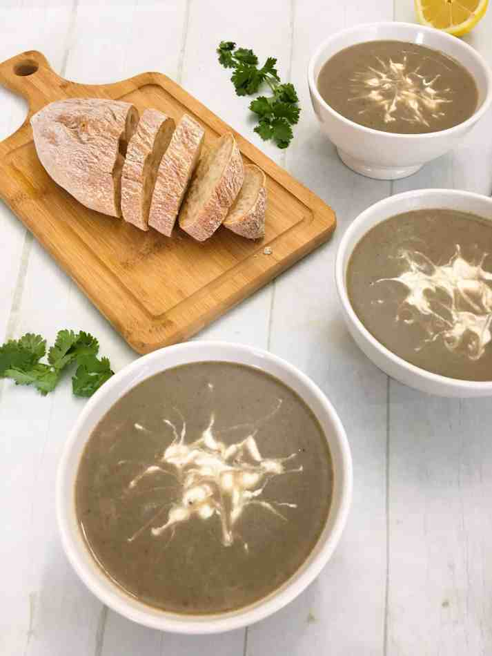 three bowls of mushroom soup with loaf of bread on cutting board