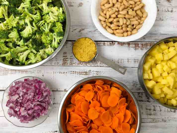 bowl of broccoli, bowl of red onion, bowl of sliced carrots, bowl of white beans and bowl of diced potatoes