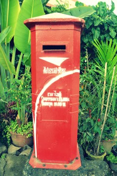 a tall lonely postbox along one of the major road in Chiang Rai, Thailand