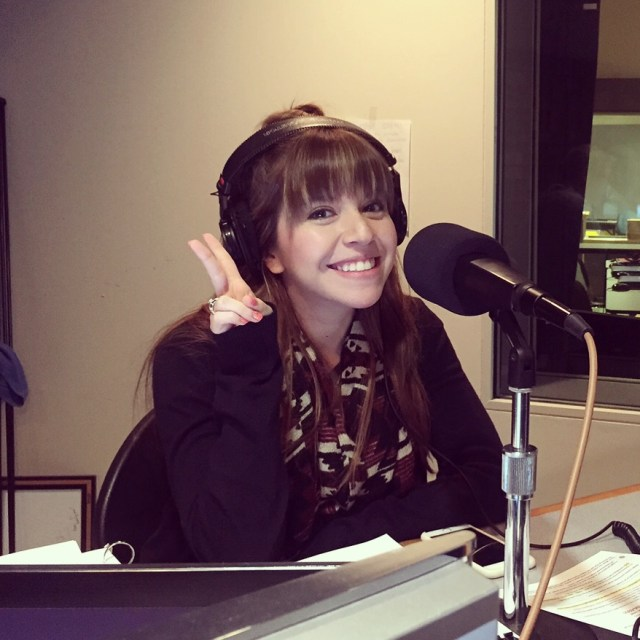 A Chicanx woman throwing up a peace sign, smiling at the camera. She's wearing over-ear headphones and is in a radio studio, behind a microphone.