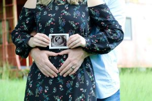 A woman holds up an ultrasound picture while her husband holds his hands in the shape of a heart over his stomach