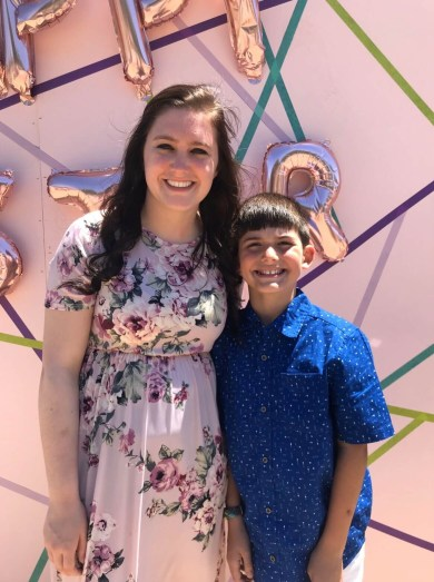 Mom and son hug in front of a backdrop at church