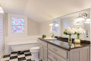 bathroom with stained glass and black and white tile