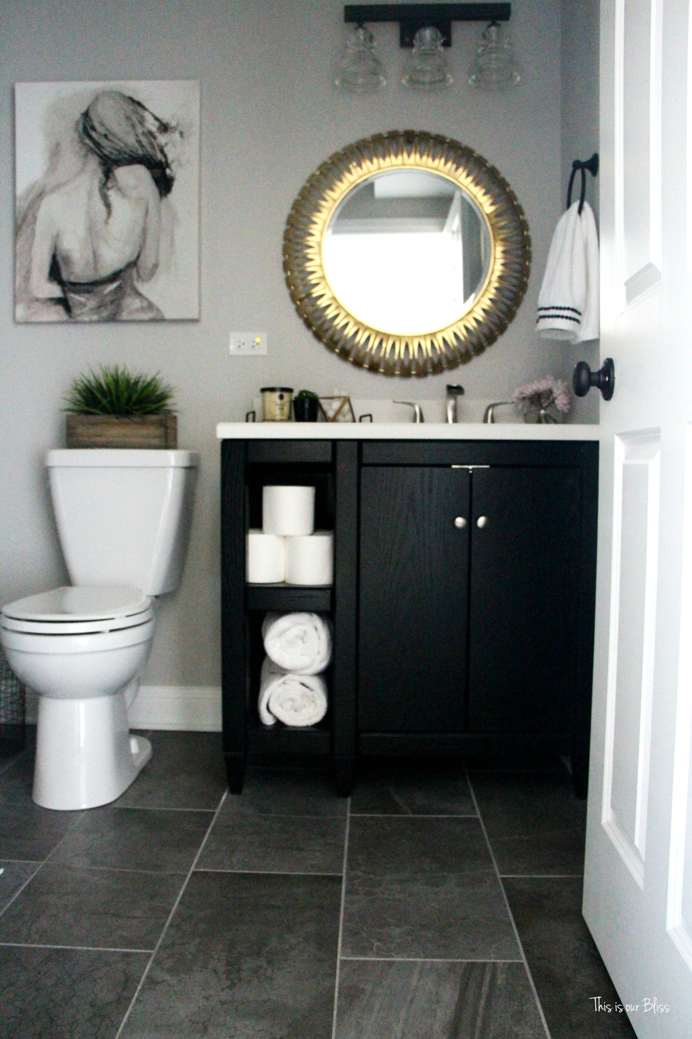 black and gold toilet. neutral glam bathroom  decor marble shower black vanity gold mirror gray tile How to create a