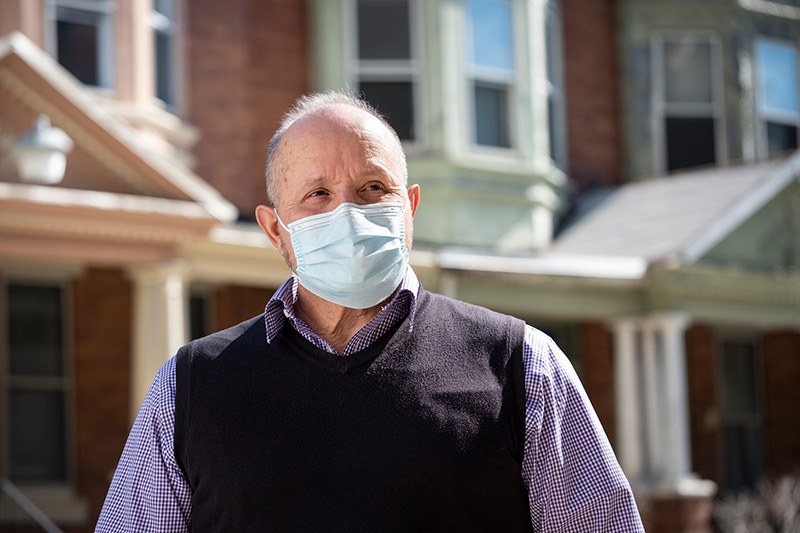 Angel Pagan, wearing a mask, standing in front of homes in Philadelphia