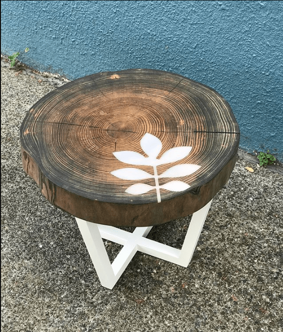 Ash wood accent table with white legs and white resin inlay of ash leaf