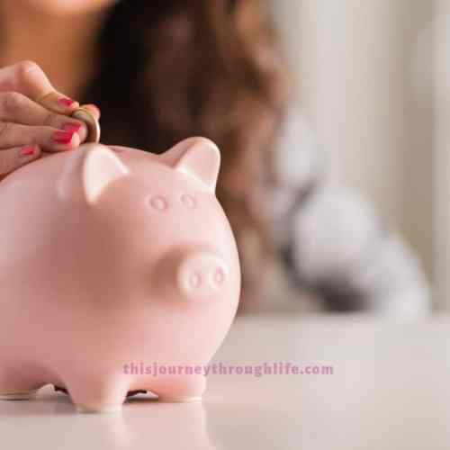 woman putting coins in a piggy bank