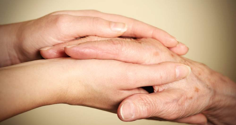 older and younger hands clasped | TJTL caring for aging parents