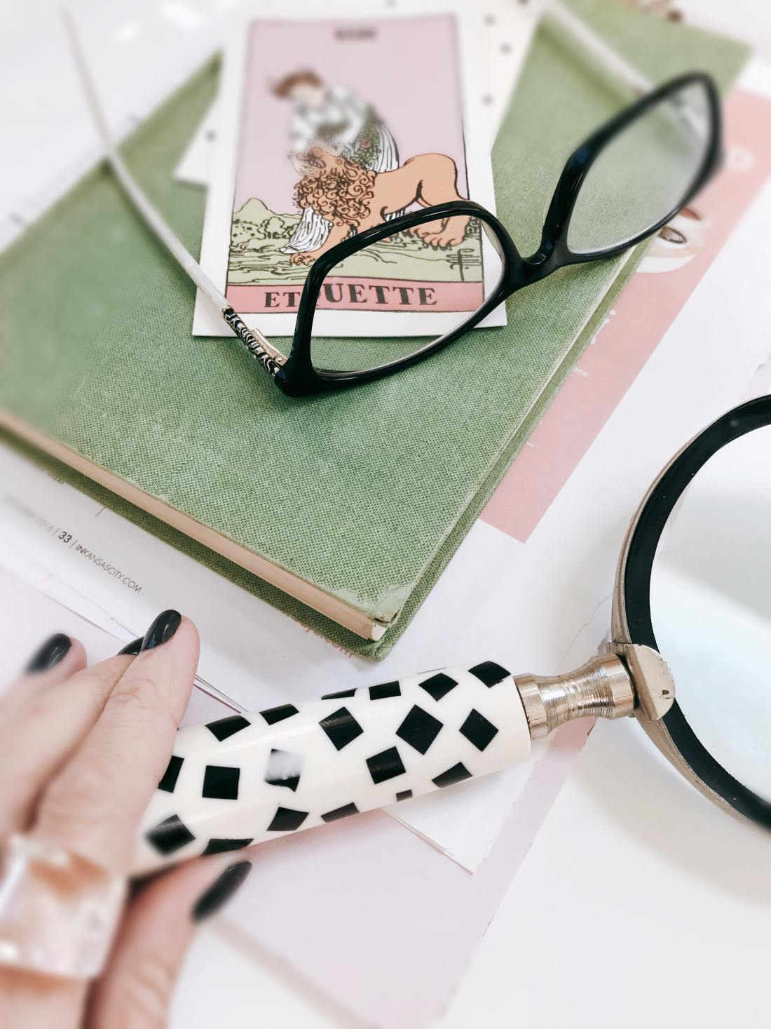 Feminine desk in pastel colours with glasses, notebooks & stationery featuring tips on how to create the best thumbnails for YouTube