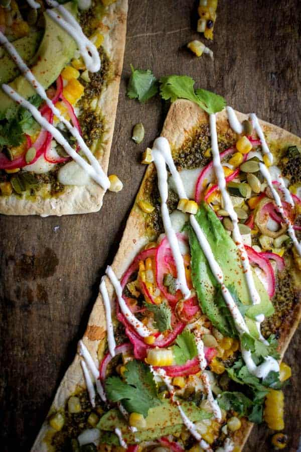 Grilled Mexican Street Corn Pizza recipe || Cilantro pistachio pesto + grilled corn + pickled red onions + avocado + cotija cheese makes for one heck of a street corn inspired pizza! || @thismessisours @flatout #spon #flatoutlove
