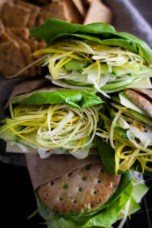 Green Goddess Sandwich recipe || These delicious sandwiches are loaded with all the sandwich essentials; butter lettuce, thinly sliced green tomatoes, cucumber, shredded carrots, a slice of Swiss, and a heaping pile of citrus pickled fennel. Plus, they are built on Ozrey One Buns that are slathered in a decadent Green Goddess sandwich spread! || @thismessisours @pitabreak #OzeryBakery #Ozery #OBCreation