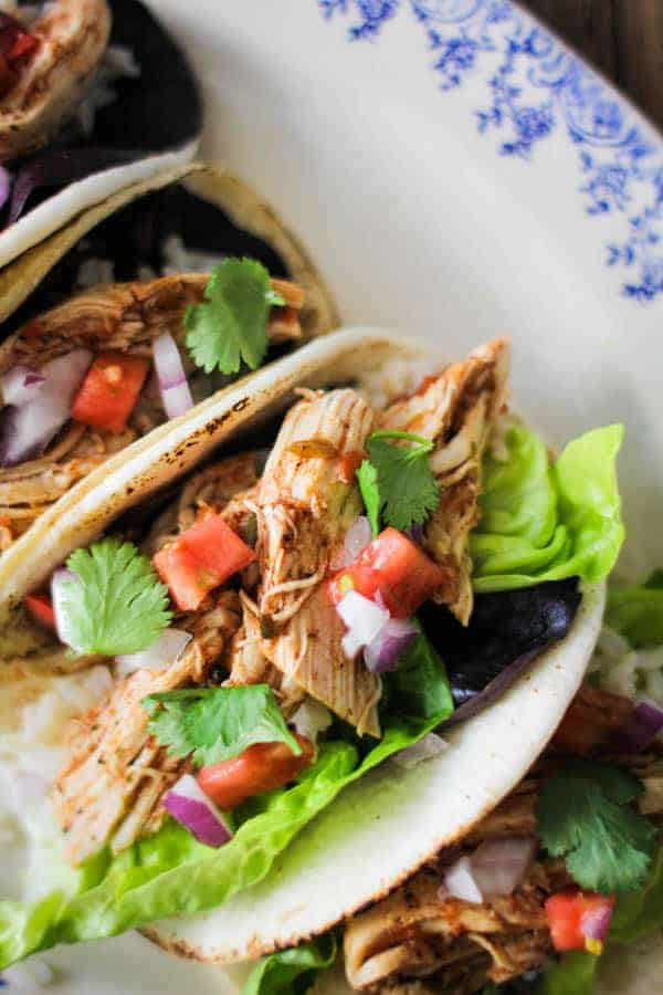 shredded salsa chicken tacos with tomato, lettuce, cilantro, and red onion