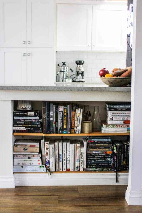 cookbook collection on shelves in kitchen