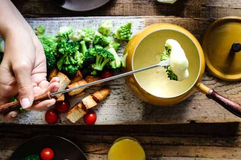 Broccoli being dipped into cheese fondue