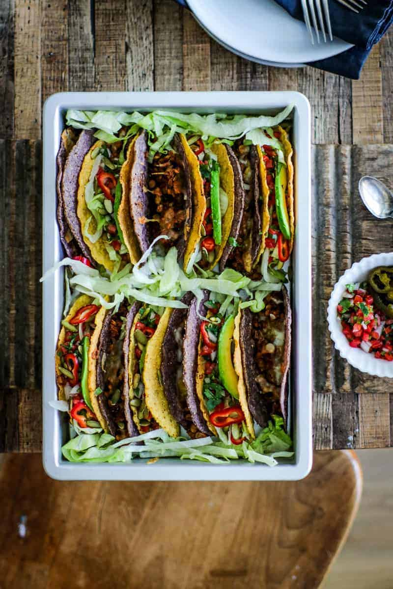 Baking pan filled with tacos made of lentils and meatless beef crumbles topped with lettuce, pico de gallo, peppers, avocado slices, and pepitas