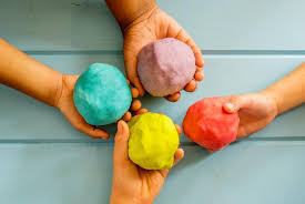 four hands each holding a ball of playdough in blue, purple, red and yellow