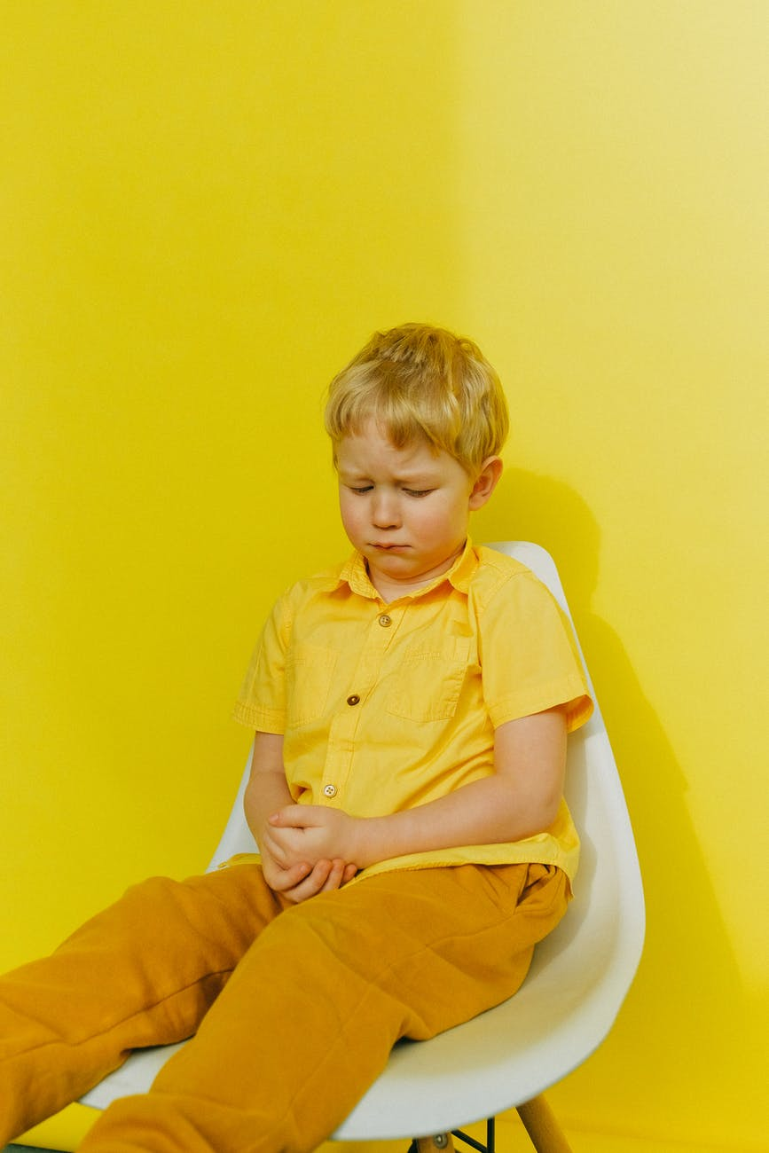 boy in yellow button up shirt sitting on white chair near wall