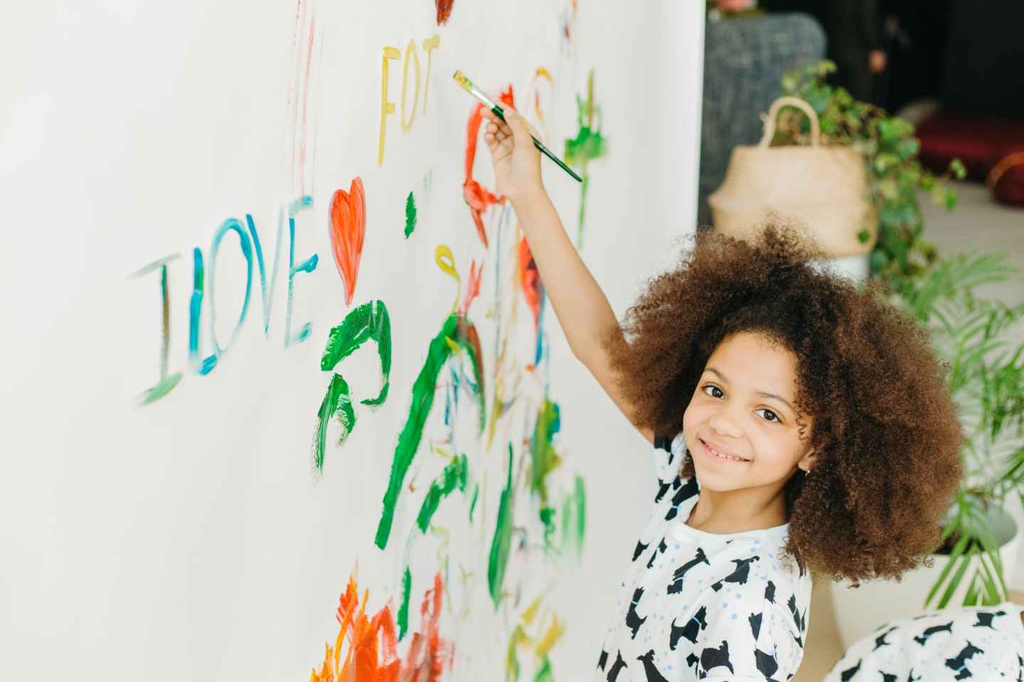 smiling girl with curly hair painting on wall