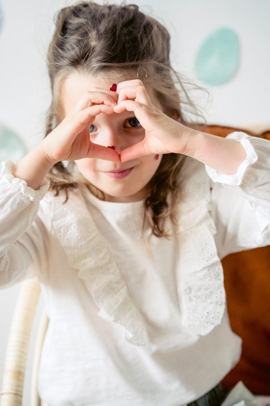 cute girl making heart gesture