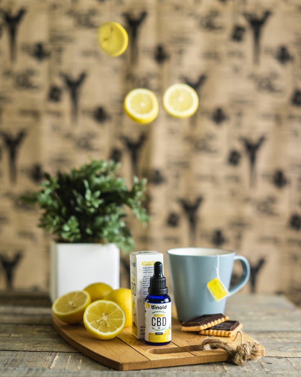 white ceramic mug with sliced lemon beside white ceramic mug on brown wooden table