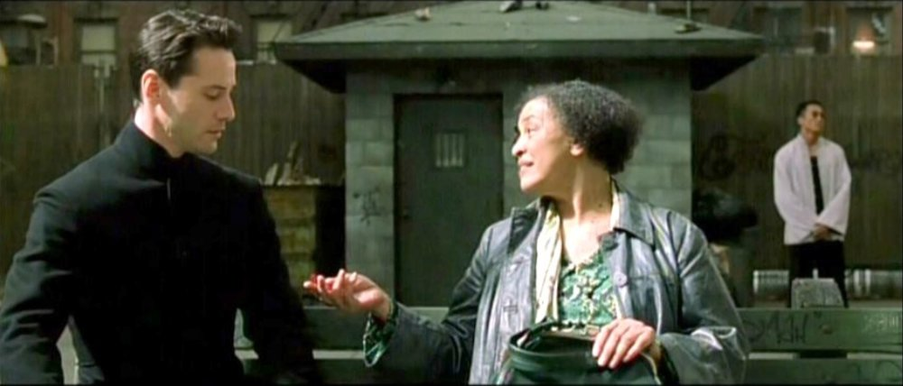 The Oracle in the movie the Matrix sitting on a bench with Neo offering him a treat