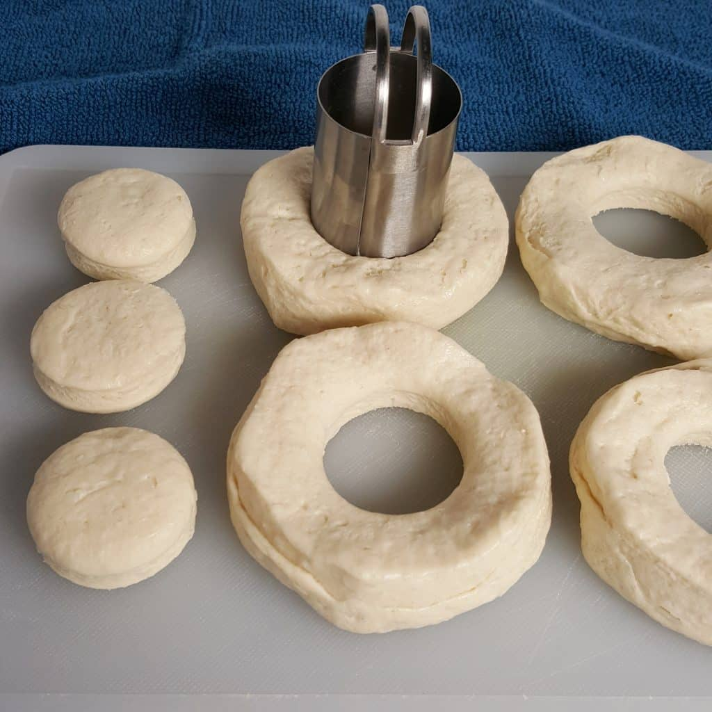 Biscuits on cutting board, using a biscuit cutter to cut out the middle