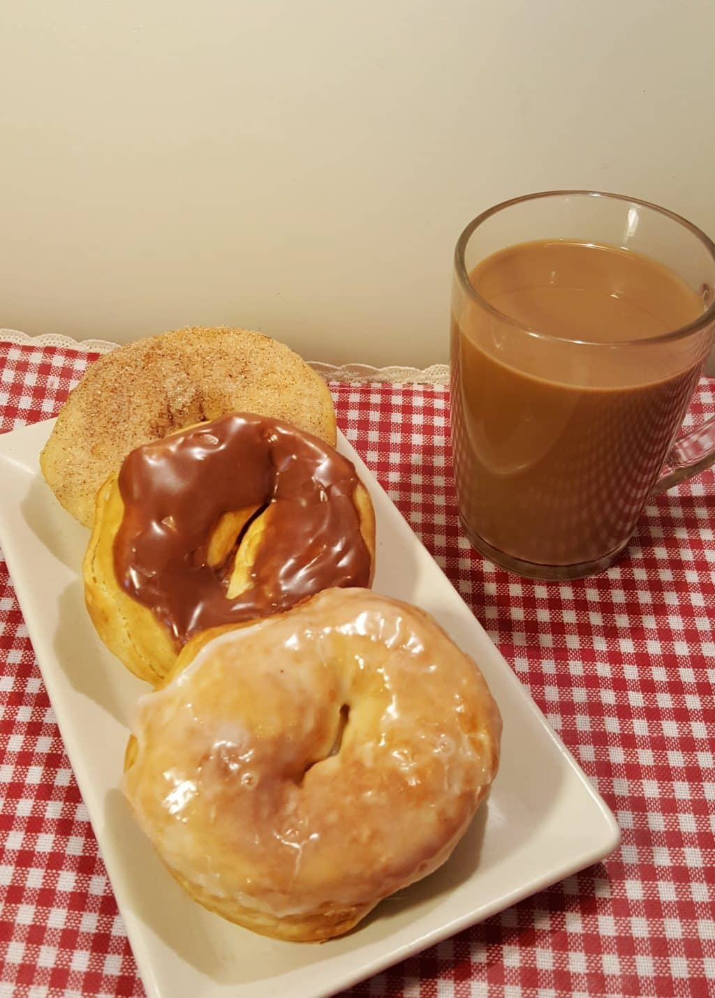 Vanilla and Chocolate Glazed & Cinnamon Sugar Doughnuts on a white plate with a cup of hot coffee.