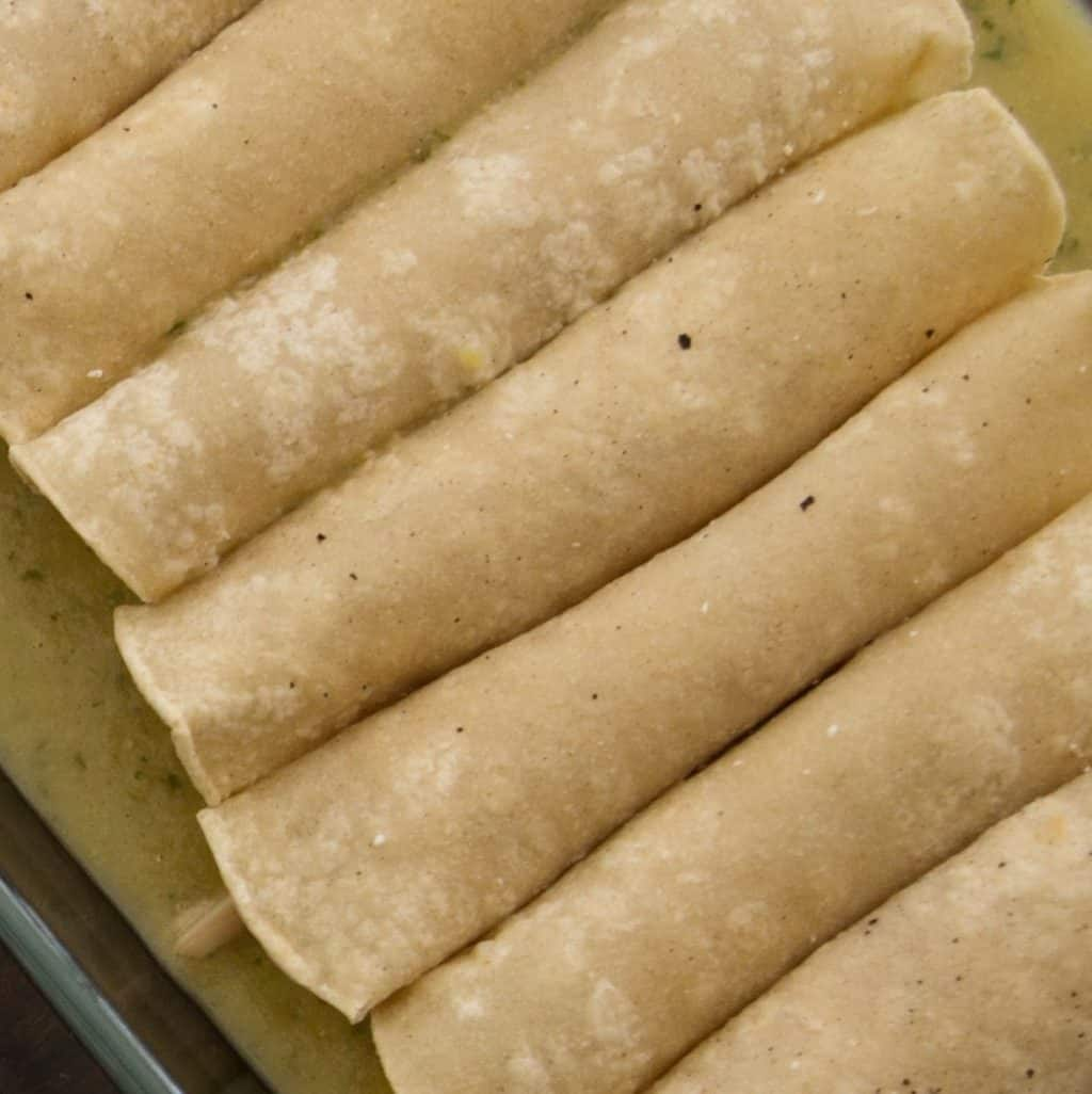 Rolled Tortillas Added to Pan of Salsa Verde