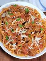Big plate of spaghetti and meatballs on a white serving platter on a rustic wood table