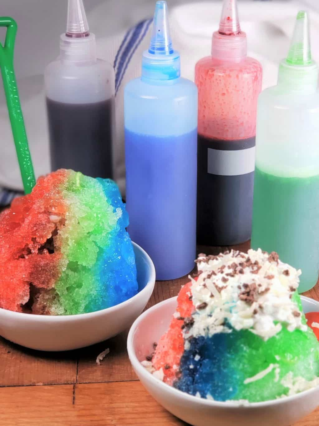 4 Bottles of Purple, Blue, Red and Green Sugar Free Shave Ice Syrup with two Shave Ice Cups in White Bowls