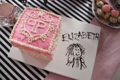 A square shaped box cake, adorned with the Plaza symbol and Eloise-style scribbles on the side. An icing drawing of the Eloise character with party girl's name.
