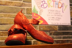 Dorothy's Ruby Slippers showcased with the invitation behind.