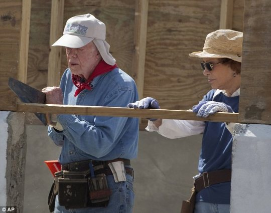 DIY: The 87-year-old former U.S. President Jimmy Carter (left) put volunteers half his age to shame by chipping in, alongside wife Rosalynn (right), to help build a series of one-room houses on the earthquake hit island of Haiti