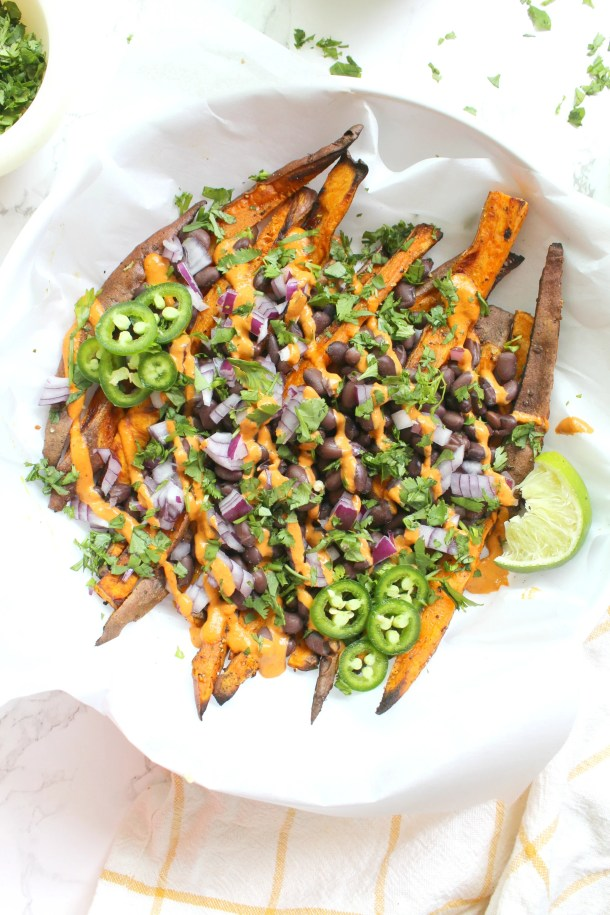 These Loaded Sweet Potato Fries with Vegan Chipotle Sauce are the perfect party snack. Sweet potato fries are baked until crispy then topped with beans, red onion, cilantro and a spicy chipotle tahini sauce   ThisSavoryVegan.com #thissavoryvegan #loadedfries #vegan