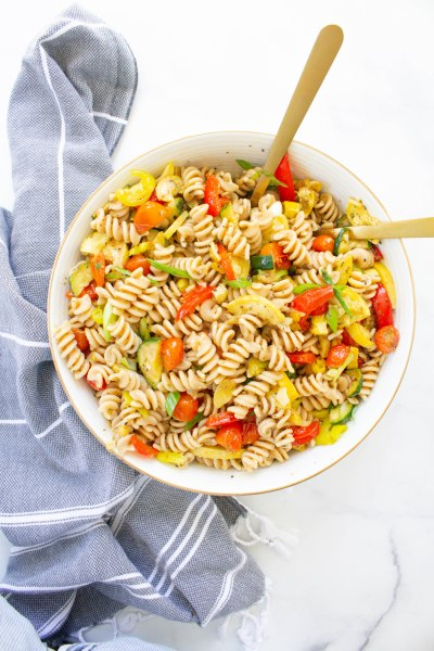 This Roasted Veggie Pasta Salad is the ultimate party side dish. Loaded with tons of veggies, whole wheat pasta and a tangy dressing | ThisSavoryVegan.com #thissavoryvegan #veganpastasalad #vegansidedish