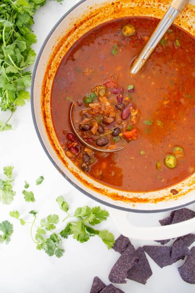 This 3 Bean Taco Soup is a hearty vegan meal - filled with soyrizo, 3 beans, salsa and taco seasoning. Top it off with fresh cilantro and spicy peppers | ThisSavoryVegan.com #thissavoryvegan #vegansoup #vegan