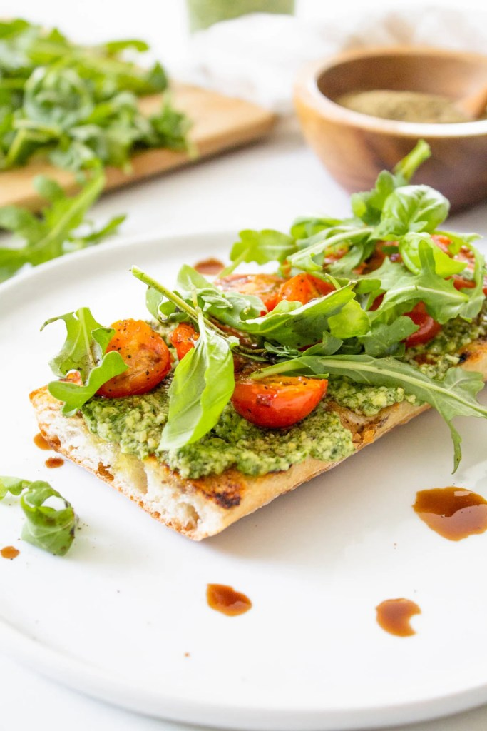 These Open-Faced Burst Tomato & Pesto Sandwiches are flavor-packed with seasoned tomatoes, vegan basil pesto, arugula and balsamic vinegar | ThisSavoryVegan.com #thissavoryvegan #veganpesto #vegansandwich
