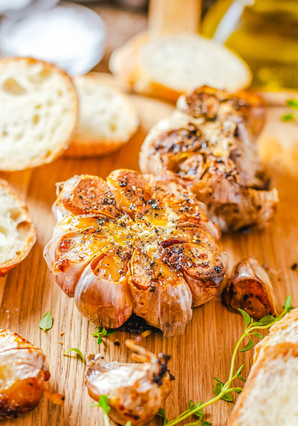 Finished Roasted Garlic on wooden board with herbs and bread slices.