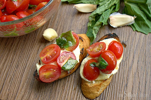 Bruschetta with Whipped Feta and Grilled Crostini, grilled baguette smeared with creamy whipped feta spread and topped with fresh grape tomatoes marinated in a sweet and tangy basil vinaigrette.