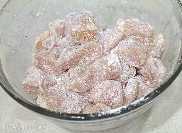 Start by preparing the chicken, dice chicken breasts into 1/2 inch to 1 inch pieces. Place in a bowl and add the cornstarch, flour, onion powder, garlic powder and pepper. Toss until all the chicken pieces are coated.