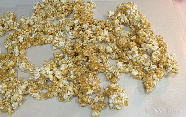 When popcorn is as evenly coated as possible, lay it out onto parchment paper in an even layer, squishing it down with a spatula or spoon.