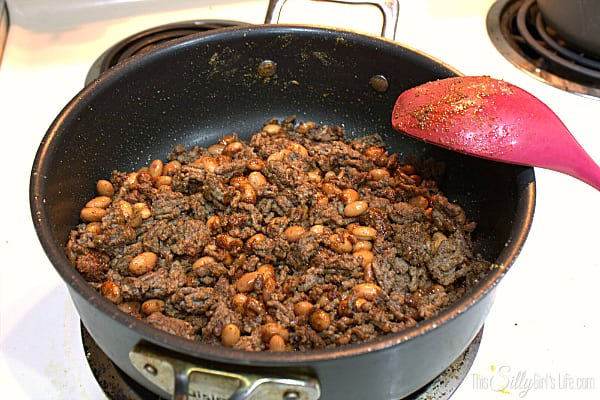 Preheat oven to 400 degrees. Brown ground beef over medium heat in skillet. Drain fat, add in the pinto beans and seasonings for the taco meat. Mix and let the seasonings coat the meat and cook until fragrant about 30 seconds.