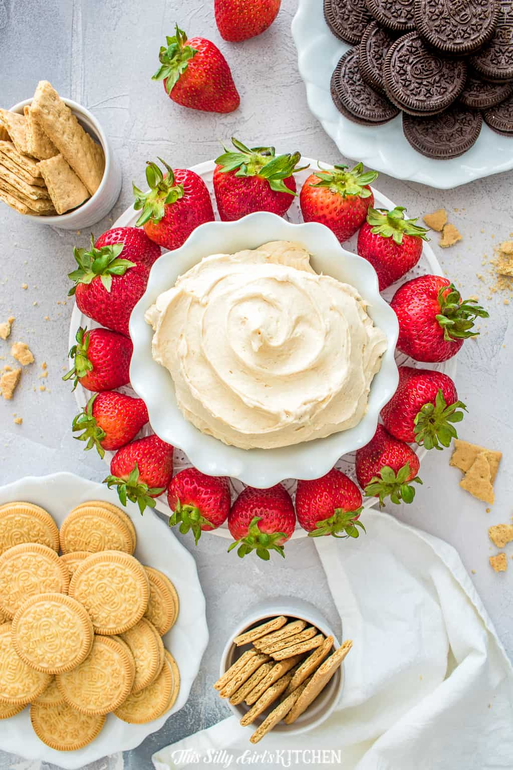 Overhead of bowl full of dip surrounded by cookies, and strawberries