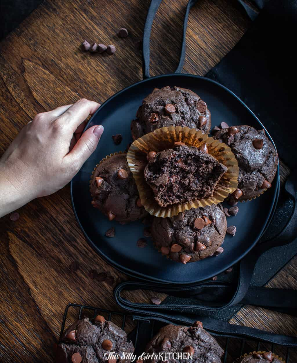Hand holding plate of muffins with one muffin in liner broken in half