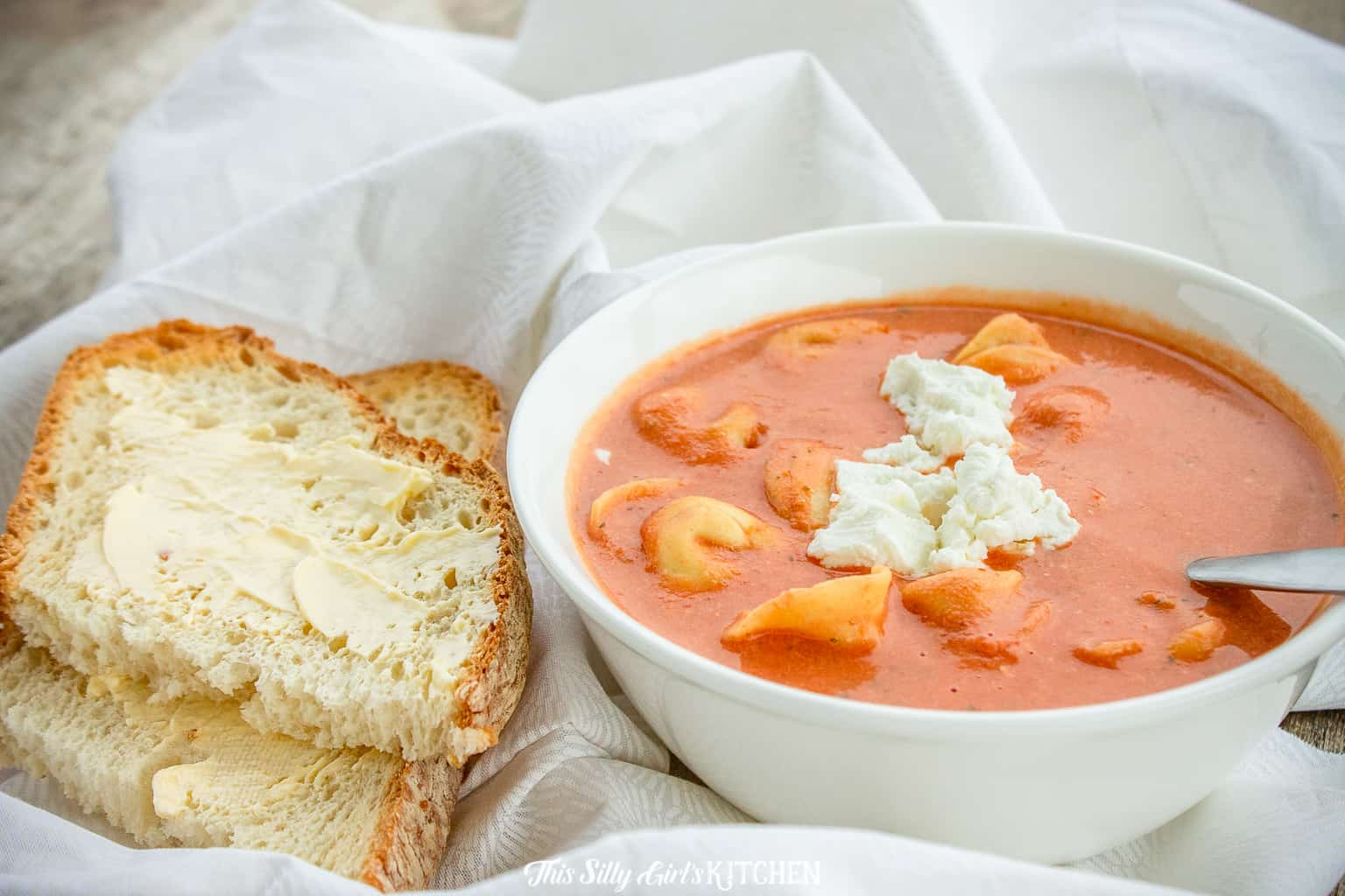 Bowl of soup with spoon in it with bread with butter beside bowl