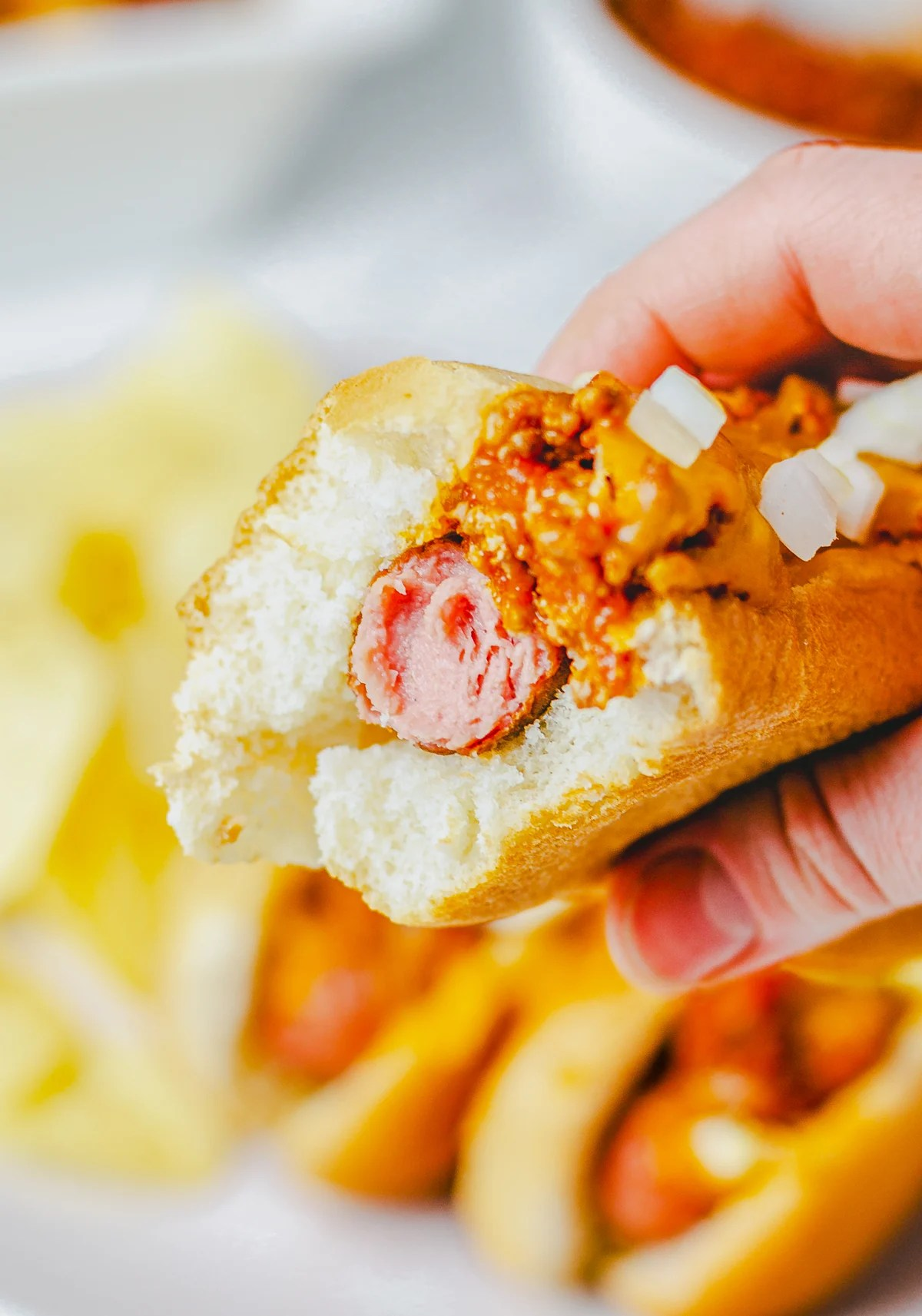Bite taken out of hot dog being held by hand